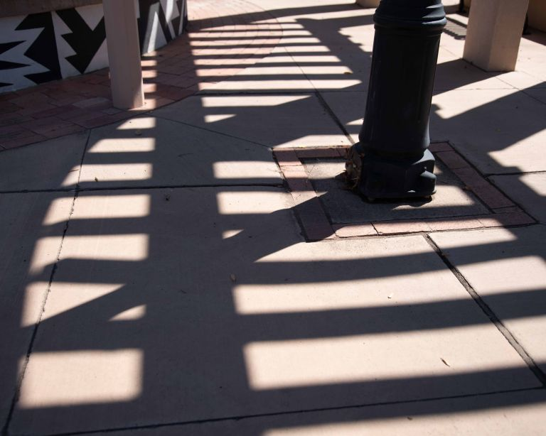 A pergola above casts some interesting shadows along with the poles.