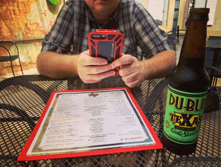 Menu and beer bottle on a table, with a guy holding a cel phone.