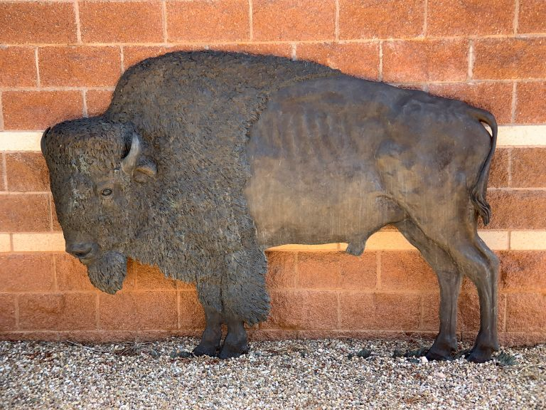A bronze sculpture of a bison against a brick wall.