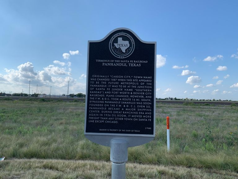 Historical marker in front of the train tracks.
