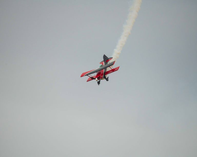 Aerobatic plane in the sky with smoke trail.