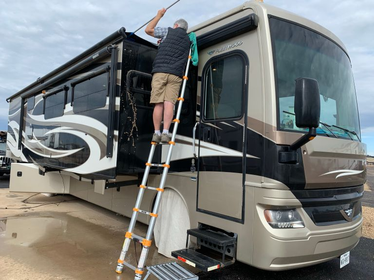 A man on a ladder, propped up against the slideout of an RV.