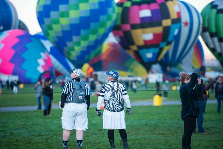 Two referees watching a hot air balloon launch.
