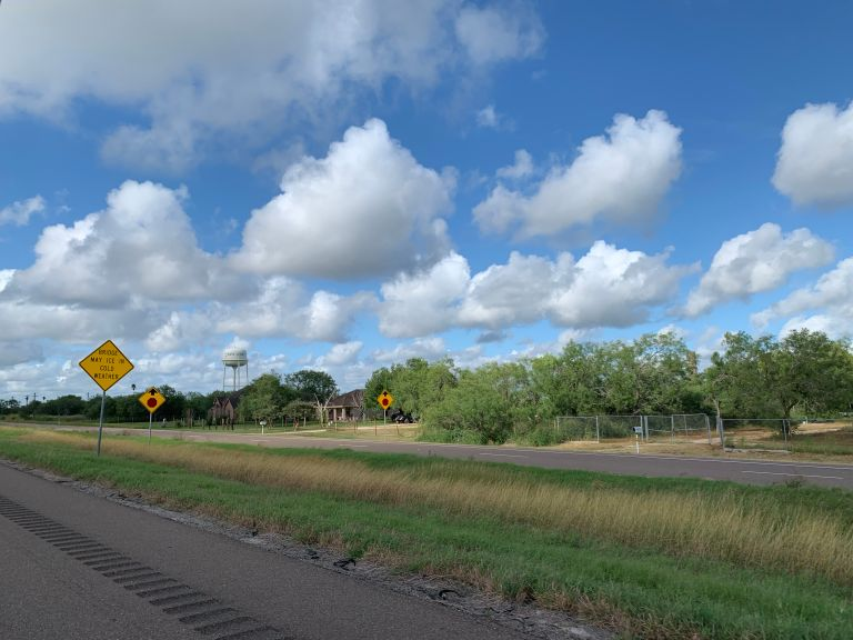 Road, grassy areas, trees, and clouds.
