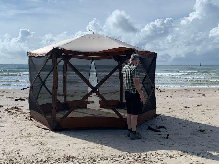 A man next to a pavilion tent.