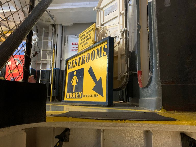 A restroom sign in black and yellow, pointing downwards.