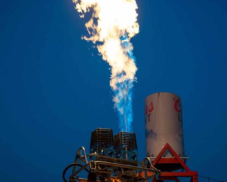 One hot air balloon burner aiming upwards, in front of a Coors Light tower.