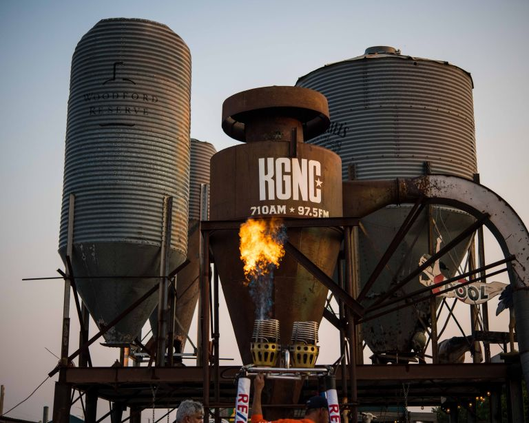 One hot air balloon burner aiming upwards, in front of four towers.