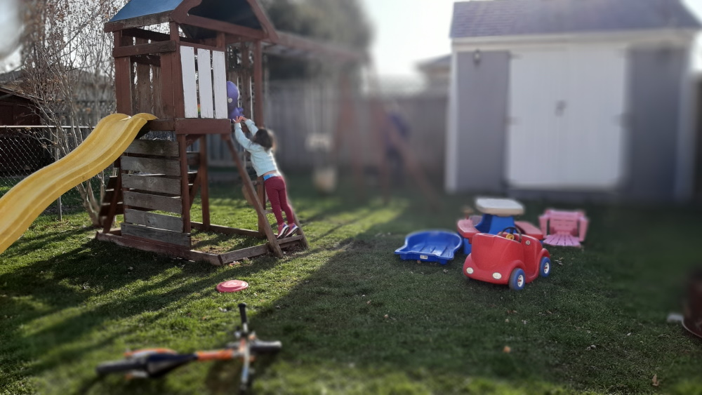 child in backyard playing foster parents