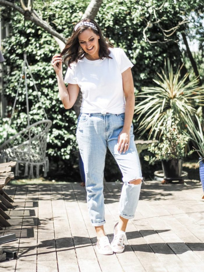 white tee styled with light mom jeans and glitter trainers