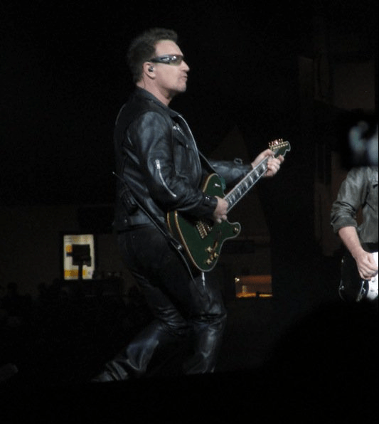 Bono playing the guitar on stage