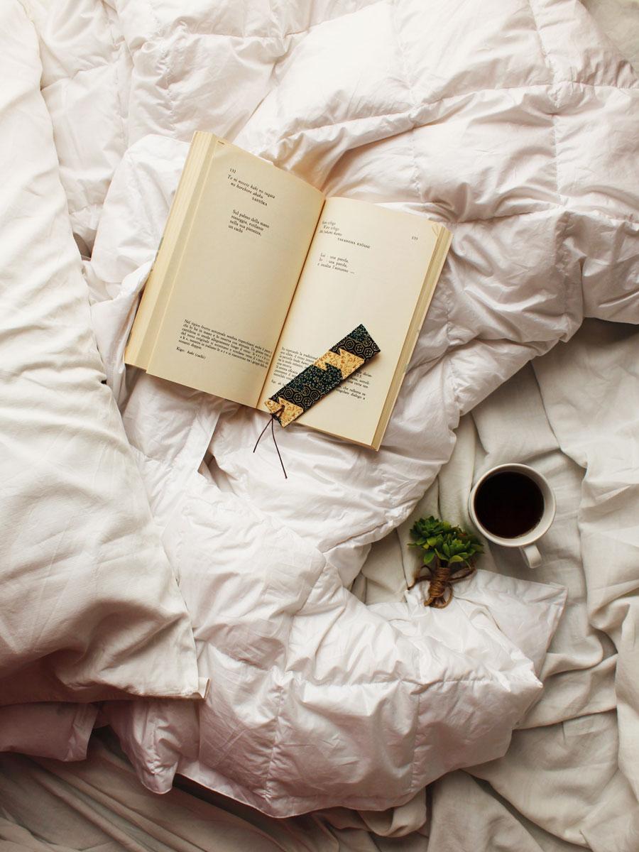 libro e tazza di tè su letto con piumino daunenstep d800 mid season