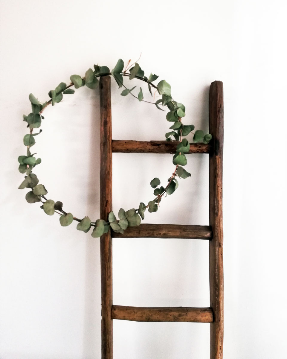 ghirlanda con rami di eucalipto su scala di legno
