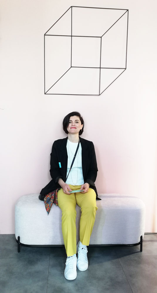 Angela seduta su una panchina Kestile sotto il cubo scultura in ferro di Antonio Sciortino.