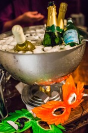 Ice bucket with bottles in and a feather mask