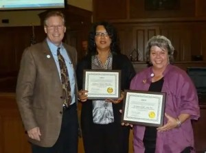 Commissioner Chairman Walter Petty presents the CERA certificates to. Pandora Paschal (center) and Dawn Stumpf (right)
