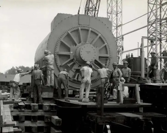 View of generator looking East while preparations are being made to skid generator off railroad car - Aug. 2, 1956