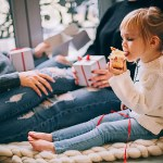 girl eating cupcake while sitting beside woman in blue denim distressed jeans for Christmas