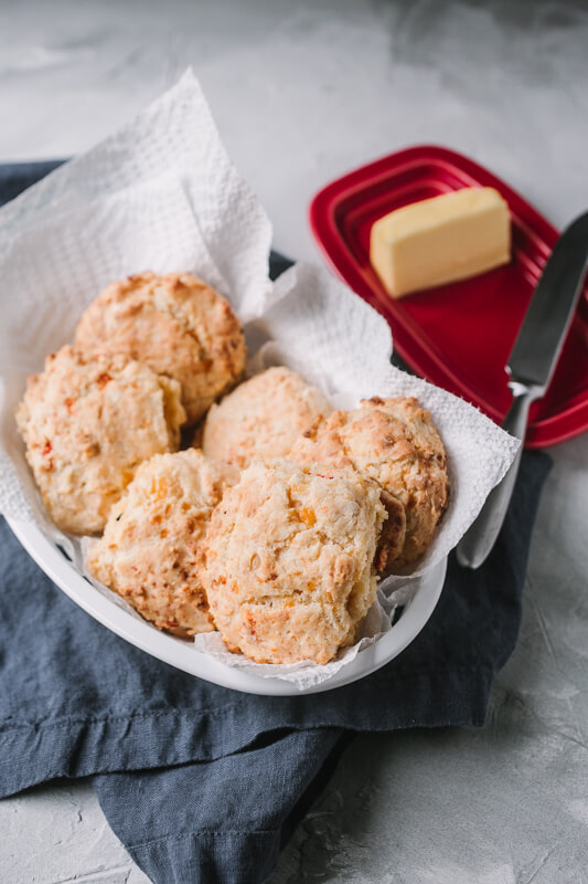a basket of pimento cheese biscuits with a butter dish in the background