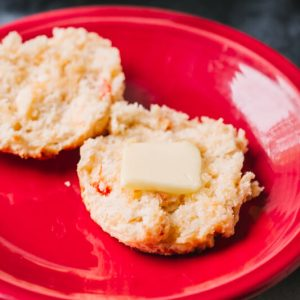 a pimento cheese biscuit on a plate with a pat of butter