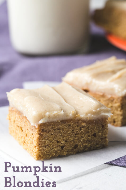 a close-up photograph of a pumpkin blondie with cream cheese icing with a glass of milk in the background