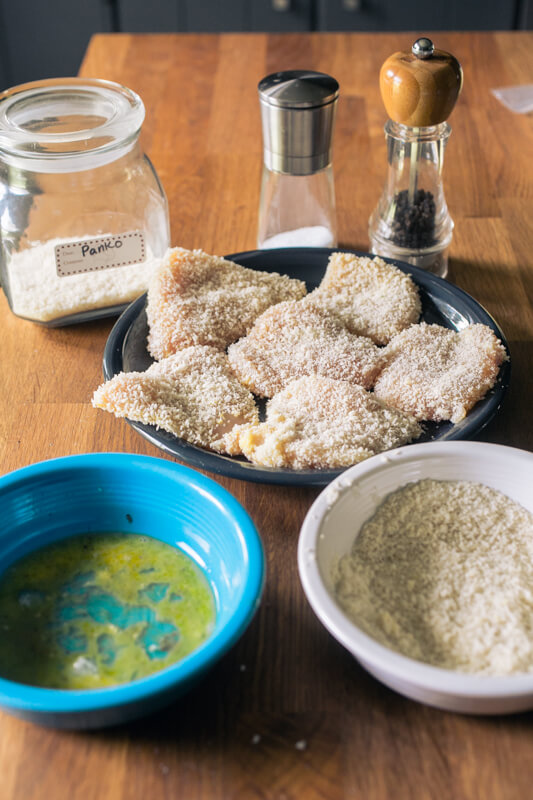 a picture of a plate of panko-breaded chicken with a bowl of egg wash and a bowl of panko crumbs in the front