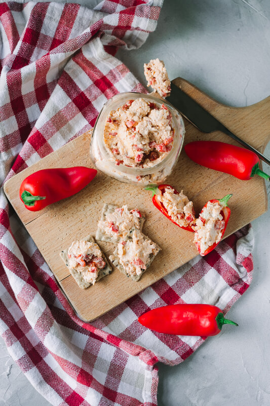 An overhead picture of a jar of pimento cheese on a cutting board with mini red peppers and crackers