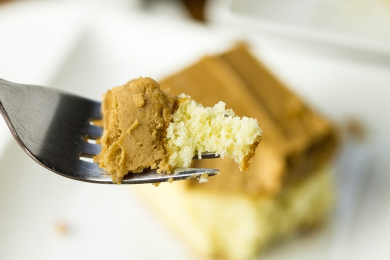 a close-up photograph of a forkful of caramel sheet cake