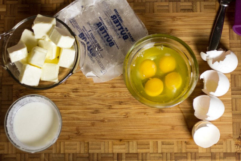 a photograph of cracked eggs and cubes of butter on a cutting board