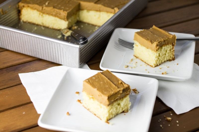 a photograph of two slices of caramel cake on plates with a pan of cake in the background