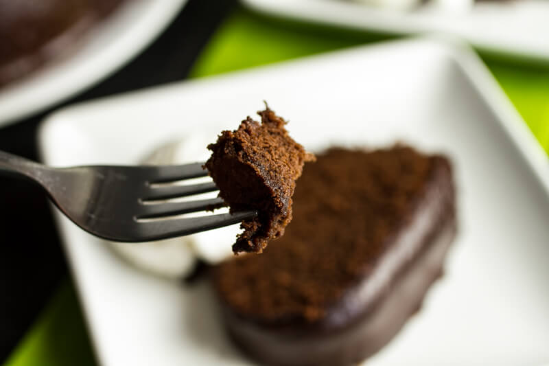 a photograph of a fork holding a bite of chocolate stout bundt cake with a slice of chocolate stout bundt cake on a plate with a scoop of ice cream in the background