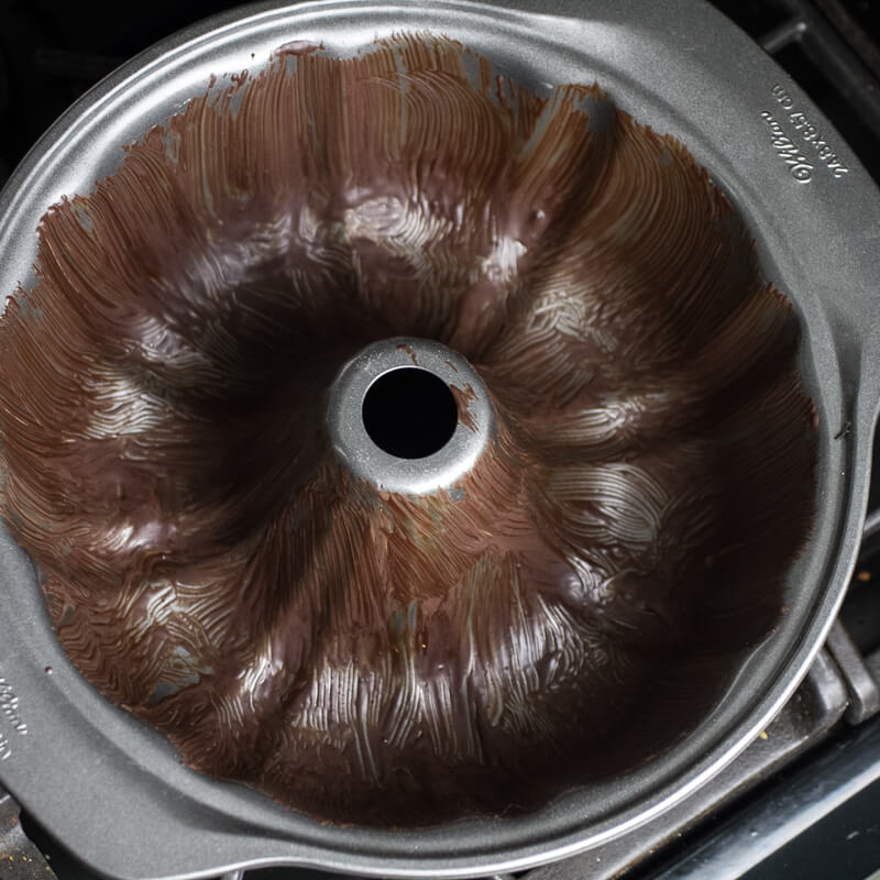 an overhead photograph of a bundt pan prepped with oil and cocoa powder
