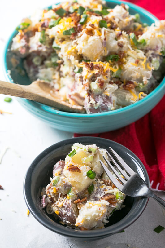 a small bowl of loaded baked potato salad with a larger bowl of loaded baked potato salad in the background