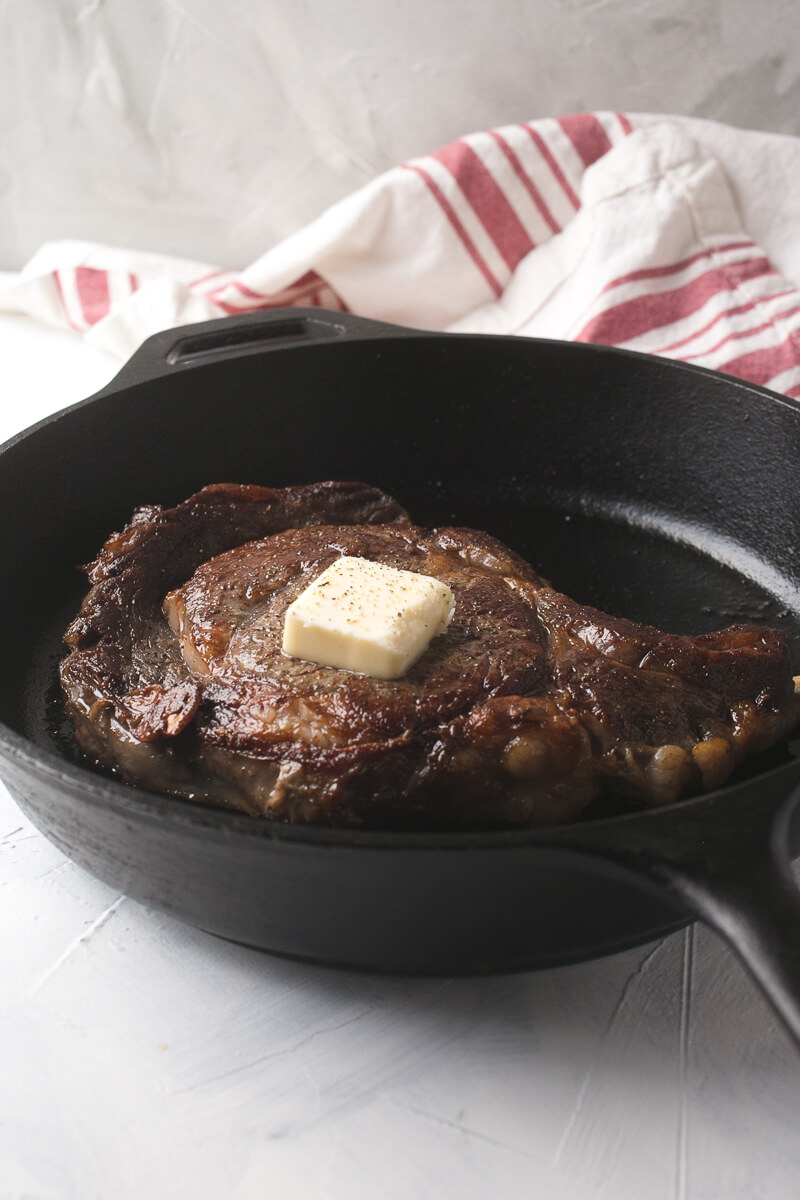 a photograph of a ribeye steak in a cast iron skillet with a pat of butter on top