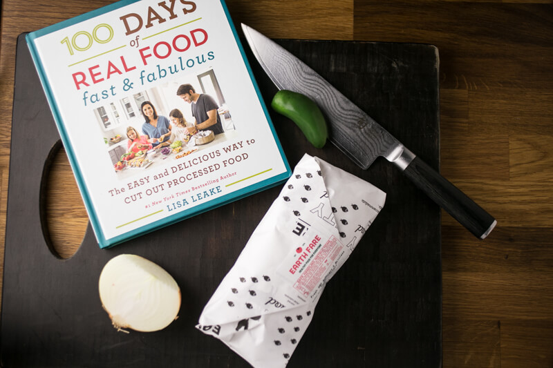 a photograph of a 100 Days of Real Food Fast & Fabulous cookbook on a cutting board with half an onion, a package of chicken, a jalapeño, and a knife