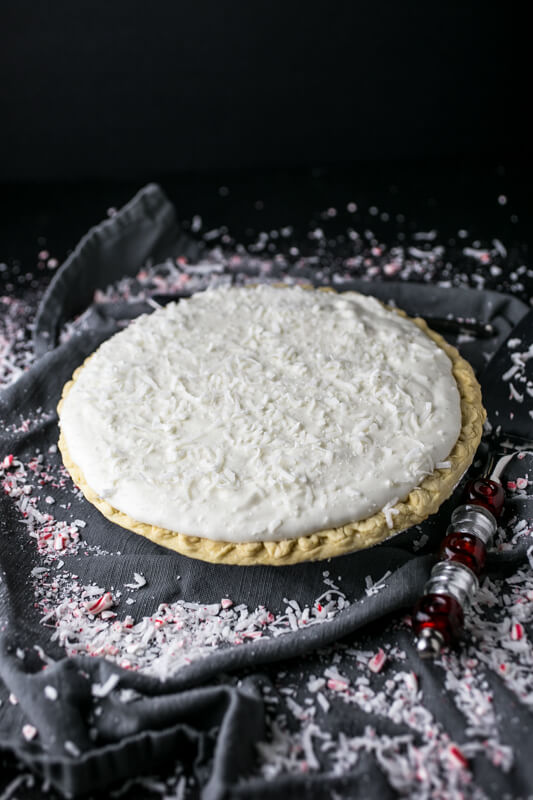 A photograph of a Christmas pie with coconut and crushed pineapple sprinkled on the backdrop