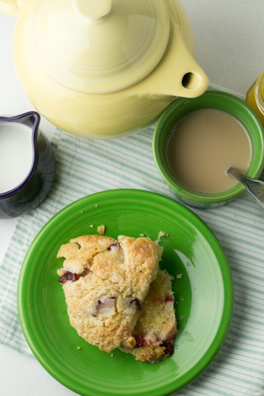 an overhead picture of a scone with plums and Greek yogurt with a teapot, a cup of tea, and a pitcher of cream