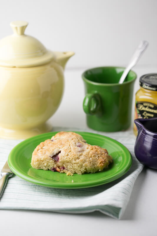 a picture of a scone with plums and Greek yogurt with a teapot, a cup of tea, a pitcher of cream, and a jar of lemon curd in the background
