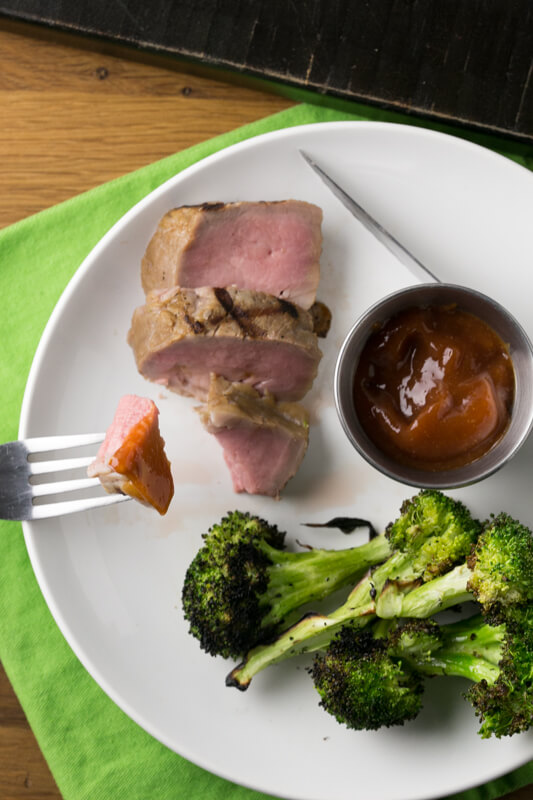 an overhead picture of slices of sweet tea brined grilled pork tenderloin with broccoli and sauce