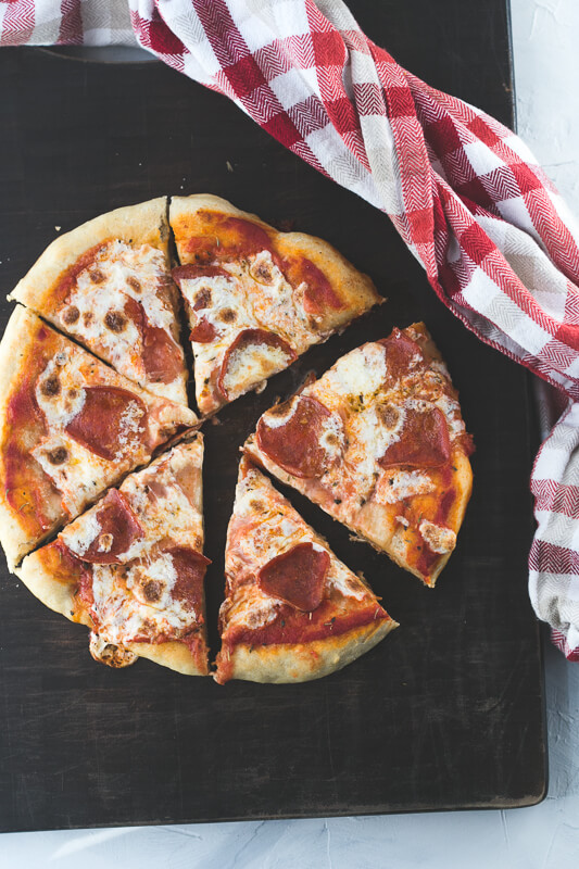 an overhead photograph of a sliced pepperoni skillet pizza on a cutting board
