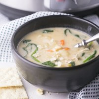 A bowl of chicken and gnocchi soup with crackers