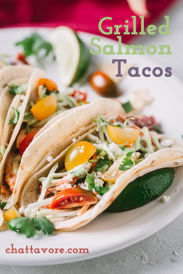 a picture of grilled salmon tacos with colorful tomatoes, slaw, and limes in corn tortillas on a white plate