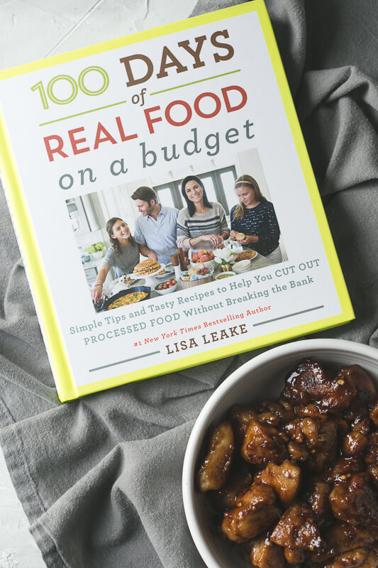 an overhead photograph of the 100 Days of Real Food on a Budget cookbook with a bowl of easy Chinese chicken in the foreground