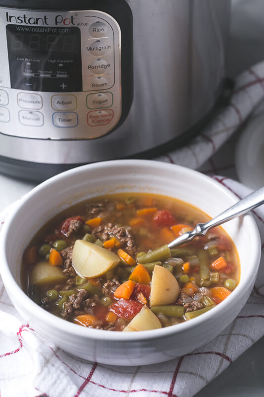 a photograph of a bowl of Instant Pot vegetable beef soup with a spoon and an Instant Pot in the background