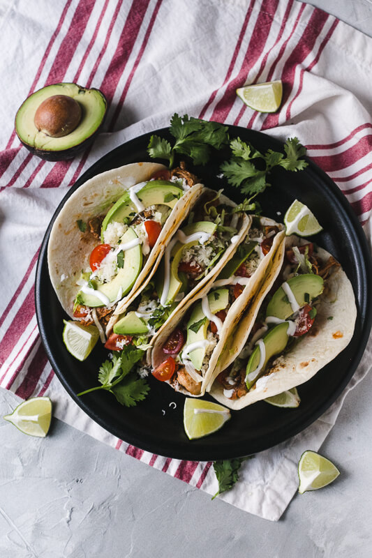 an overhead photo of a plate of Instant Pot chicken tacos with limes, avocado, and cilantro