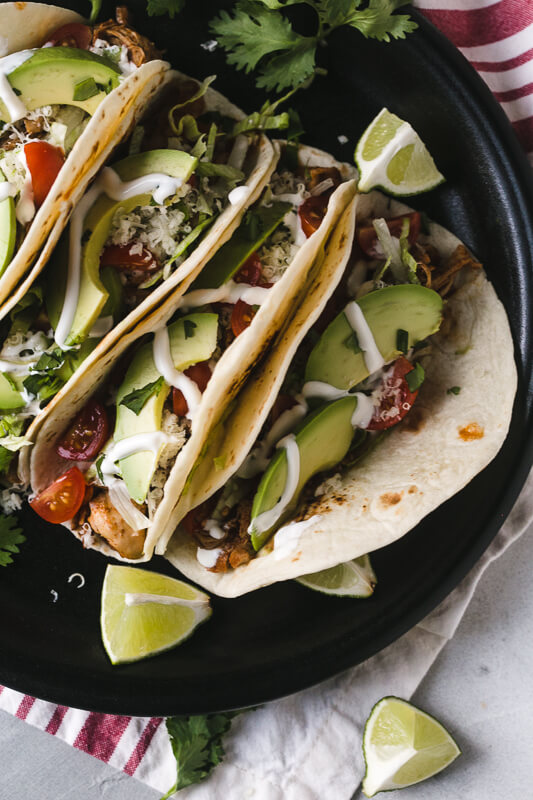 an overhead photo of a plate of Instant Pot chicken tacos with limes and cilantro