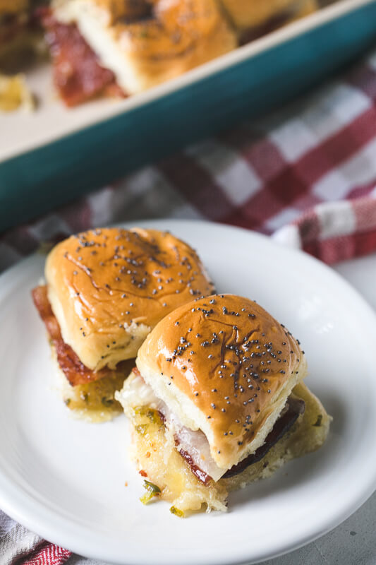 a 3/4 angle photograph of two bacon sliders with pineapple-jalapeño jelly on a white plate