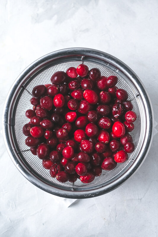 an overhead photograph of a colander full of fresh cranberries