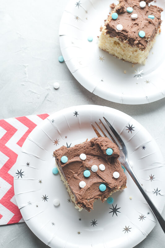 an overhead photograph of two slices of yellow cake from scratch with chocolate frosting and blue and white sprinkles