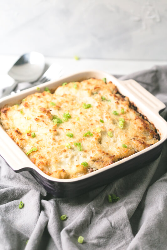a photograph of a cottage pie in a baking dish with a spoon in the background